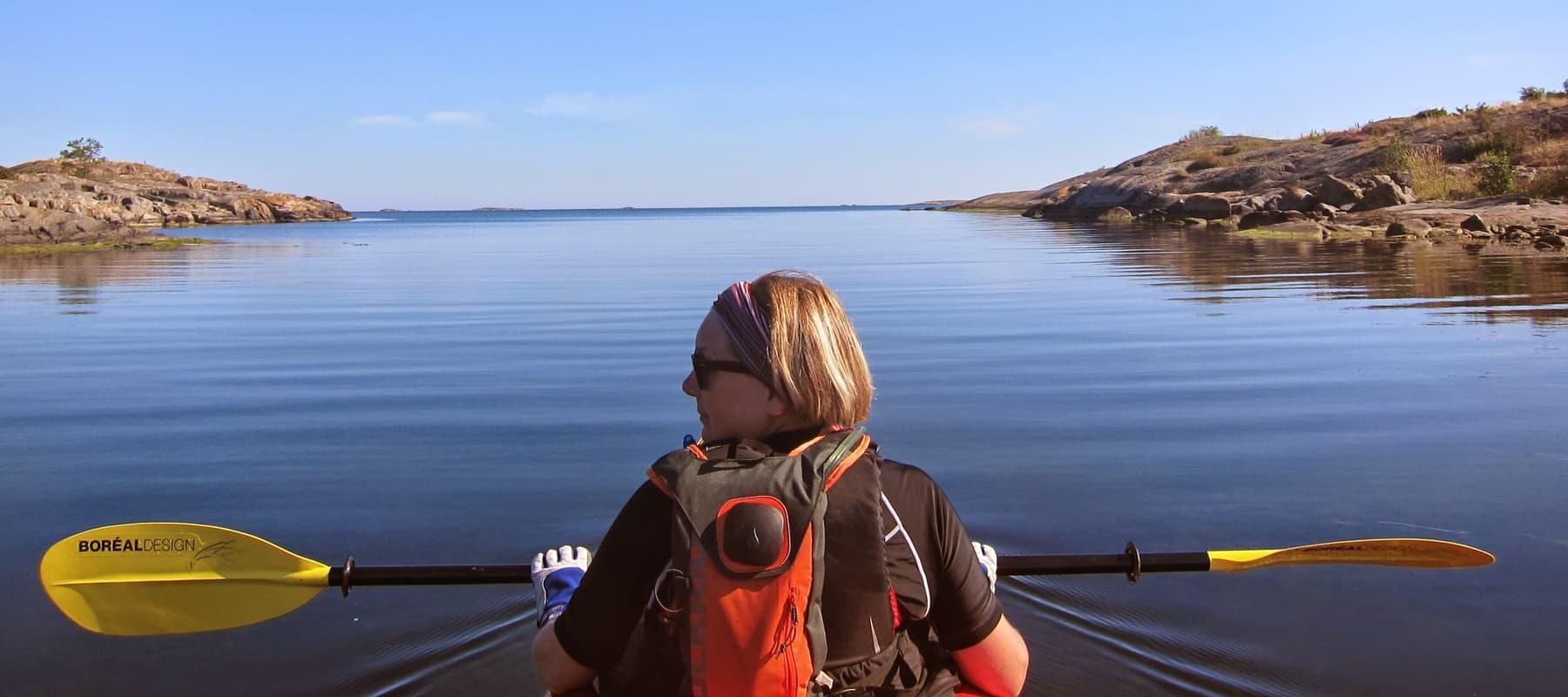 Donations. Female paddler on a still lake.